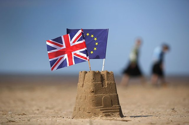 In this photo illustration the flag of the European Union and the Union flag sit on top of a sand castle on a beach on May 09, 2016 in Southport, United Kingdom