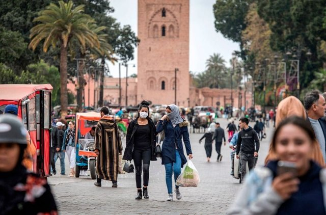 Masked women walk throguh Marrakesh's Jamaa el-Fna square (Getty Images)