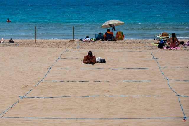 Tourists already have to stay within one of 5,000 13 by 13 feet squares marked out on the popular Poniente and Levante beaches (Photo by JOSE JORDAN/STR/AFP via Getty Images)