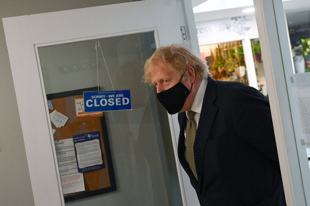 Prime Minister Boris Johnson walks past a sign reading 'We are Closed' during a visit to a Barber shop (Photo by Justin Tallis - WPA Pool/Getty Images)