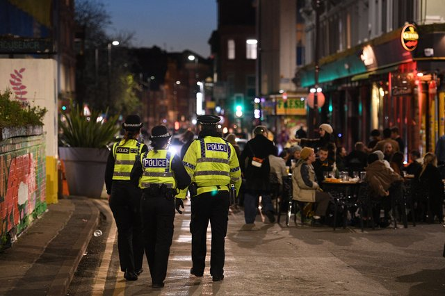Police officers patrol the streets where customers are enjoying drinks at tables outside the pubs (Photo by Oli SCARFF / AFP) (Photo by OLI SCARFF/AFP via Getty Images)