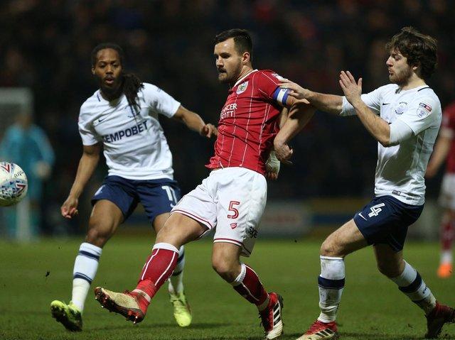 Bailey Wright is challenged by Preston midfielders Daniel Johnson and Ben Pearson at Deepdale in March 2018