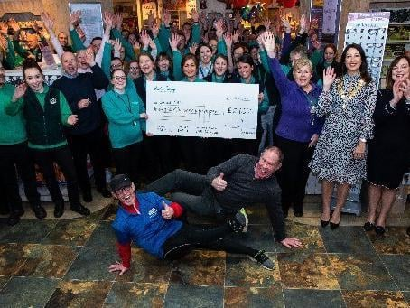 Steve Cody who completed his Cha Cha Slide plank challenge is presented a cheque by managing director of Barton Grange Garden Centre, Guy Topping.