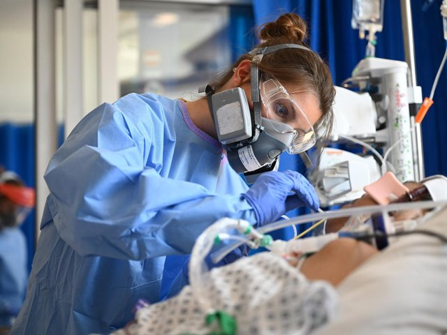 Clinical staff wear Personal Protective Equipment (PPE) as they care for a patient in intensive care