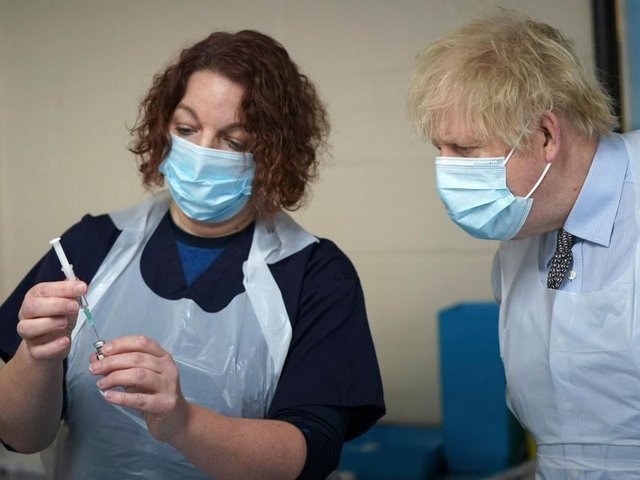 Prime Minister Boris Johnson is shown how to prepare the vaccine by advance nurse practitioner Sarah Sowden as he visits a COVID-19 vaccination centre