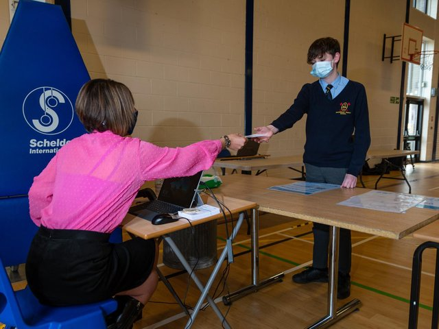 School Business Support Officer Julie Brennan hands year 8 pupil Harrison his card which he will give to a coronavirus tester. Photo: Kelvin Stuttard.