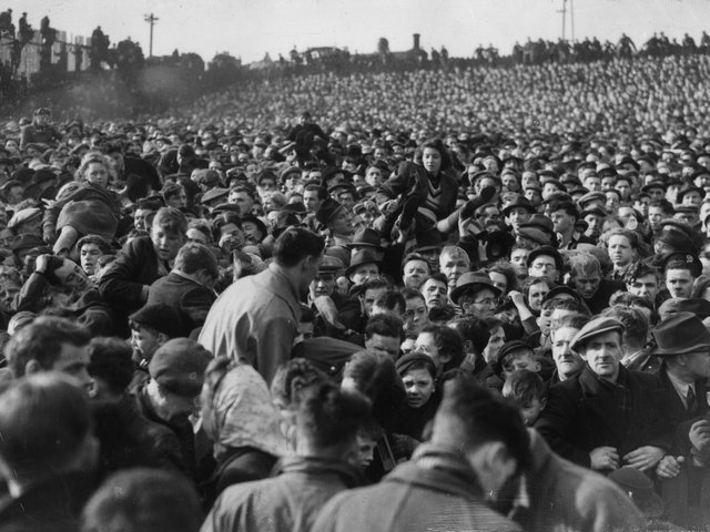 Women and children being passed over the heads of the crowd during the crush in which 33 football fans died during an FA Cup match between Stoke and Bolton Wanderers at Burnden Park, Bolton, on March 9, 1946