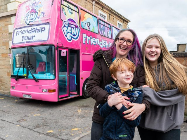 Kerry Driver with her children Leah (12) and Tyler (six) and the big pink double decker bus.