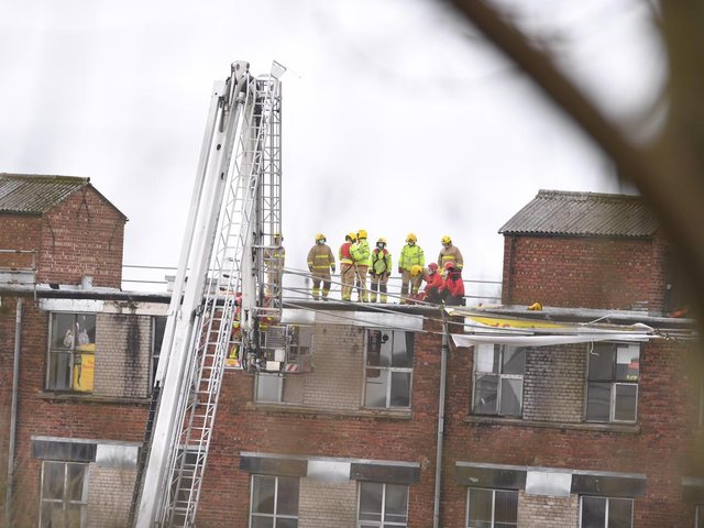 The windy weather has caused scaffolding along the roof of the four-storey building to come loose and fire crews are using a ladder platform to secure it