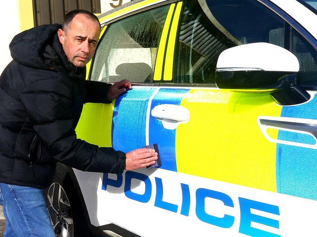 Kris Holt puts the finishing touches to one of his police cars. Picture by Tony North