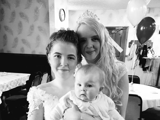 Lucy (left) and Leanne Devine with their daughter Faith on their wedding day two years ago