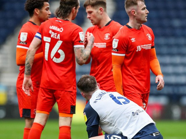 PNE defender Liam Lindsay down on his haunches as Luto's players celebrate their win