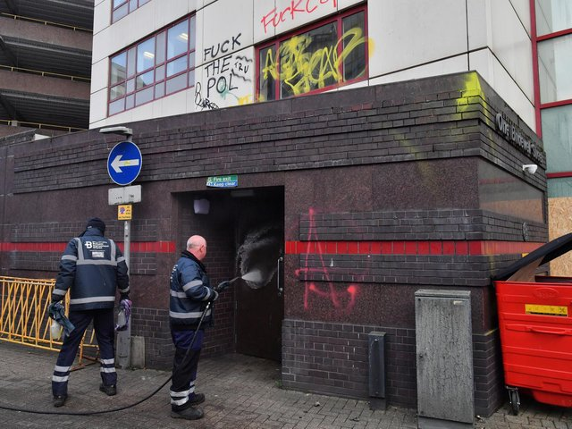 Workers from the Bristol BID Team clean graffiti outside of Bridewell Police Station in Bristol. Protesters broke windows and vandalised the police station on Sunday after demonstrating against the Government's controversial Police and Crime Bill.