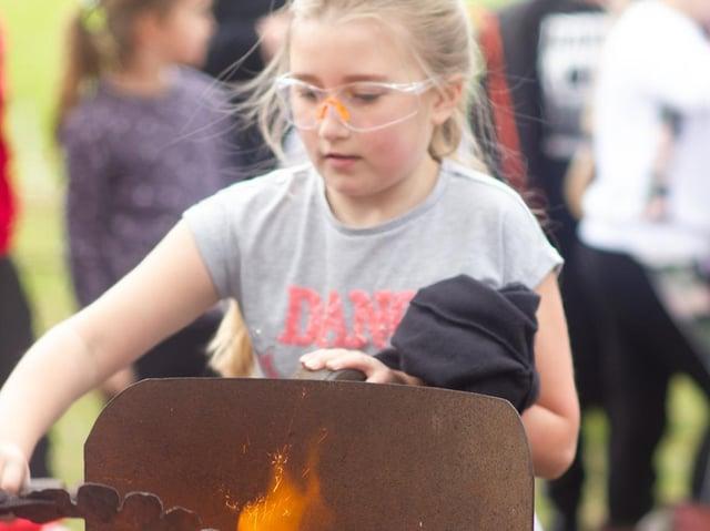 Pupil Lauren gets hands-on during the blacksmith visit, photo: Gert Schepens.