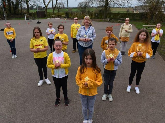Pupils and staff at Great Eccleston Cop School were a sea of yellow yesterday as they stood to remember those who had lost their lives to the virus last year.