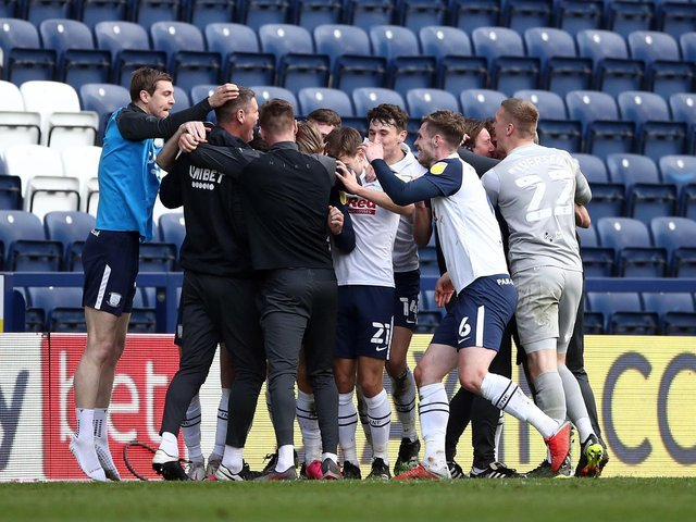 Preston North End players and staff celebrate their stoppage-time equaliser
