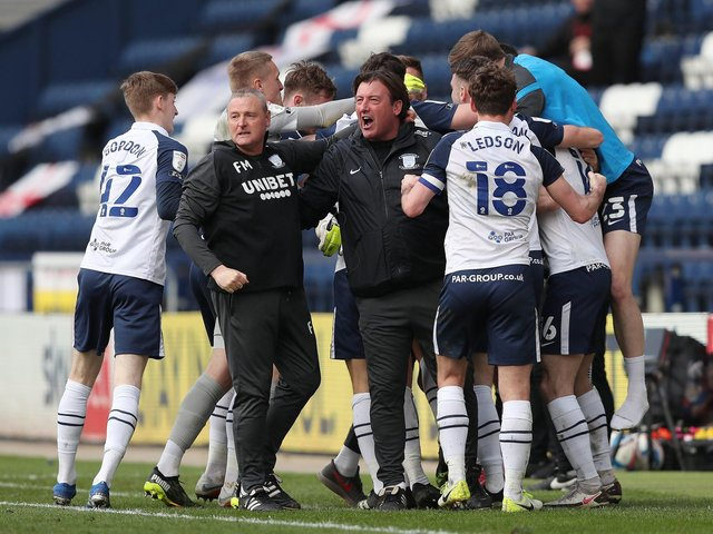 Brad Potts (hidden) is mobbed  by his team-mates and  interim head coach Frankie McAvoy after scoing his last-gasp equaliser