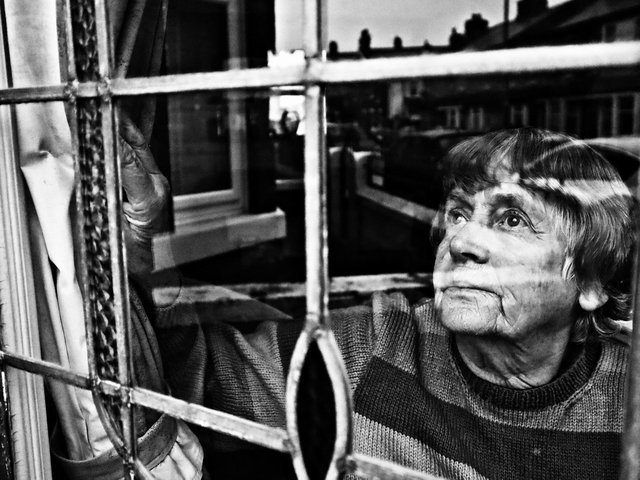 A powerful image of a woman glancing from a window in this Blackpool student's photograph. Photo by: Sammy Hall.