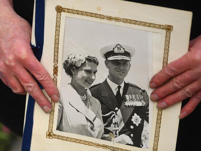 A person holds a photograph of Queen Elizabeth II and the Duke of Edinburgh outside Windsor Castle, Berkshire, following the announcement of his death at the age of 99. Picture date: Friday April 9, 2021. Picture: PA Wire/PA Images/Victoria Jones