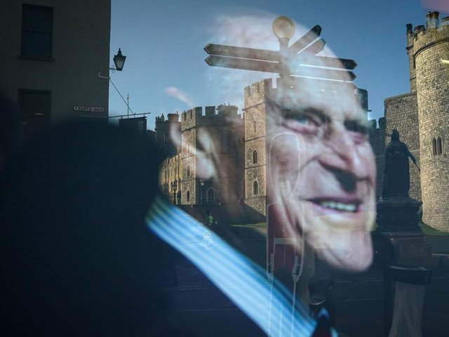 Windsor Castle is reflected in a shop window displaying a photograph of Prince Philip, Duke Of Edinburgh who died aged 99 on April 15, 2021 in Windsor