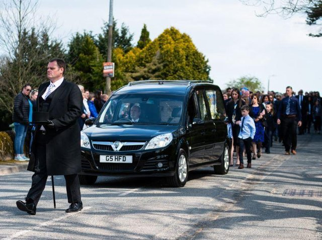 A line of mourners, including fellow pupils from John Cross C of E Primary School followed the hearse