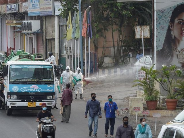Members from the Disaster Response Force (DRF) of Telangana State, wearing protective gear spray disinfectant on a street against the spread of the Covid-19 coronavirus in Hyderabad on April 19
