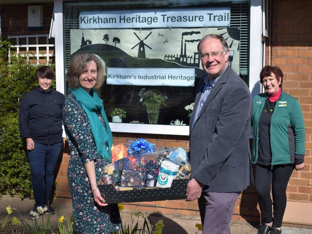 Adele and Peter Walsh (foreground) with their luxury hamper in front of their window display. They are joined by (left) artist Alex Blakey and (right) Barbara Parkinson, Morrisons Community Champion