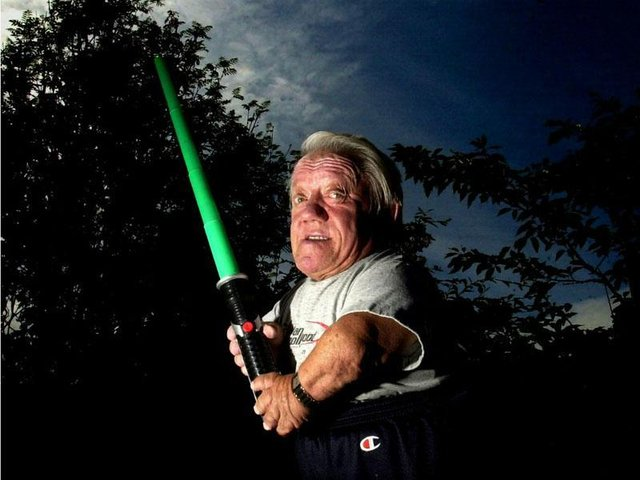 R2D2 actor Kenny Baker poses at his home in Preston with a light sabre for the 30th anniversary of the release of Star Wars: A New Hope