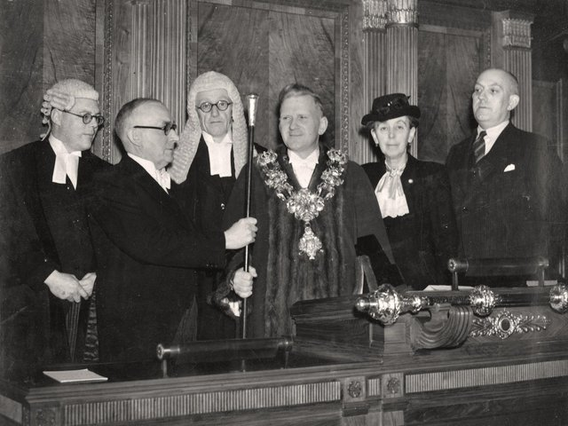 Outgoing Mayor Herbert Rhodes hands the staff of office to William Beckett in November, 1946. Also present are past mayor Alderman Margaret Pimblett and at far left, the Town Clerk, W Lockley
