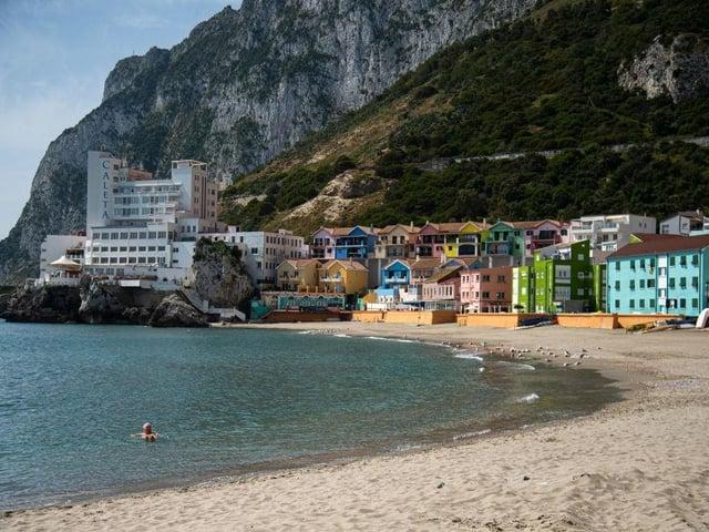 A man swims in Catalan Bay beach in Gibraltar