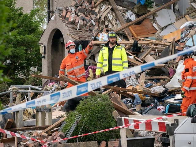 Emergency workers at the scene of a suspected gas explosion, in which a young child was killed and two people were seriously injured