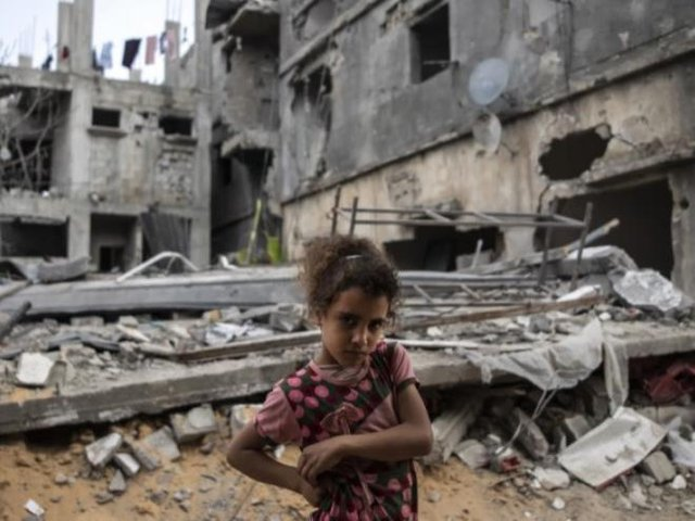 Ten-year-old Rahaf Nuseir outside the ruins of her family home in Gaza.
