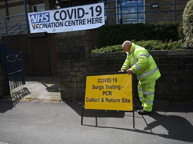 A worker sets outs a sign for a Covid-19 PCR Surge testing site, and vaccination centre, at the United Reformed Church in Blackburn