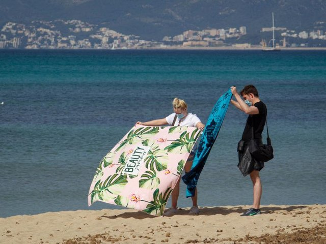 A tourist couple unfold their towels on Palma Beach in Palma de Mallorca