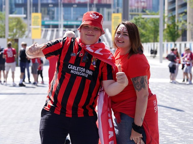 Two Morecambe fans pose outside the ground.