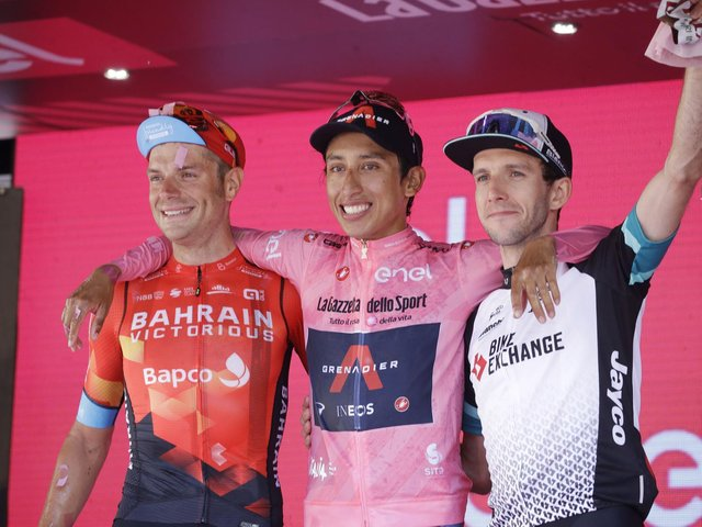 Colombia's Egan Bernal is flanked by runner-up Italy's Damiano Caruso, and Third placed Britain's Simon Yates, right, as he celebrates on podium after completing the final stage to win the Giro d'Italia cycling race, in Milan, Italy.