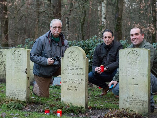 Members of the Overloon War Chronicles group by the side of gravestones in the Overloon Cemetery. Picture by albert-hendriks.