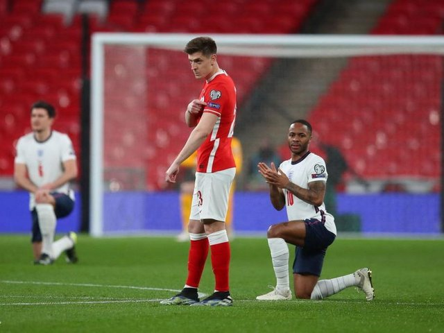 England's midfielder Raheem Sterling and the England players take a knee against racism before kick off of the FIFA World Cup Qatar 2022 Group I qualification football match between England and Poland at Wembley on March 31, 2021