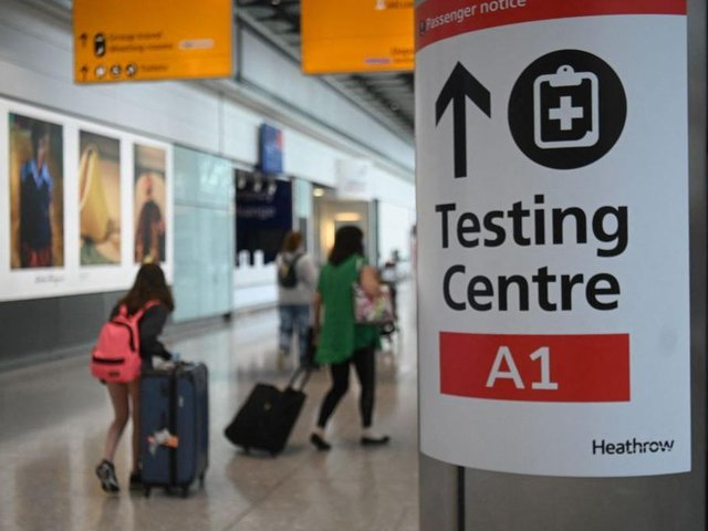 Passengers push their luggage past signage displaying the way to a Covid-19 test centre, in Terminal 5 at Heathrow airport