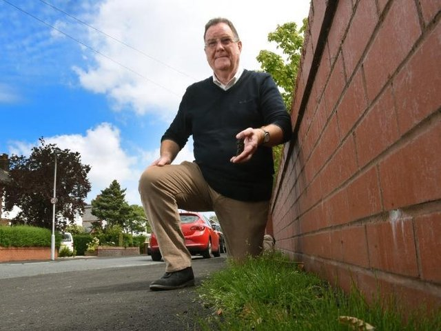 Councillor David Howarth with the weeds that have grown through the resurfacing