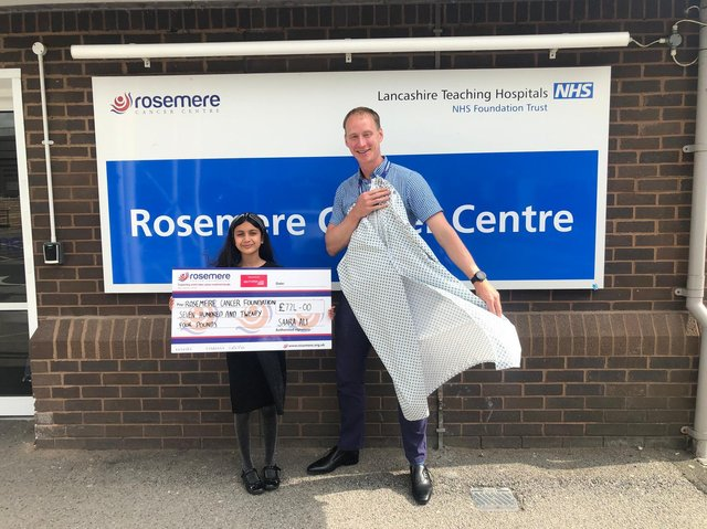 Baker Saara with Rosemere Cancer Foundation's chief officer Dan Hill and one of the 500 radiotherapy wraps/gowns her donation has bought
