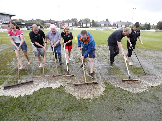 Standing water is swept off the pitch at Bamber Bridge's Sir Tom Finney Stadium