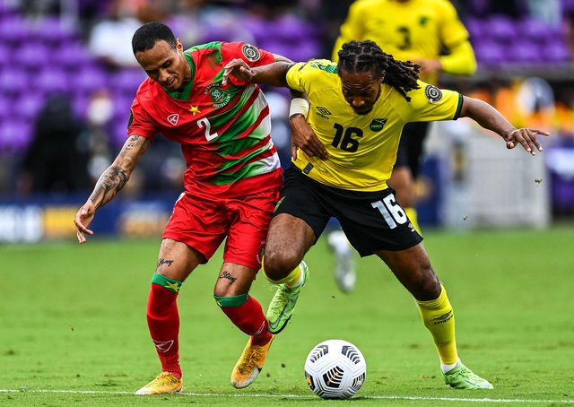 Jamaica's Daniel Johnson battles with Suriname's Damil Dankerlui (left)  during the Gold Cup group match at the Exploria Stadium in Orlando, Florida (Photo: CHANDAN KHANNA/AFP via Getty Images)