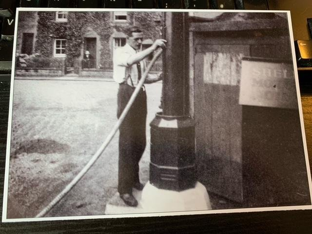 Early 1920s photo of George Lamb using a manual petrol pump at his garage near the fountain at Hornby.